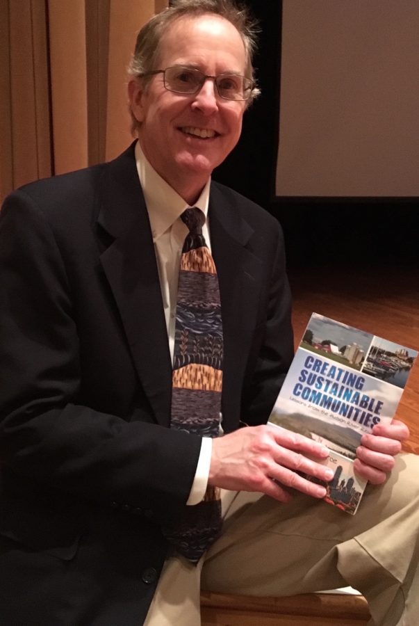 Author, environmentalist and professor Rik Scarce with his novel, Creating Sustainable Communities.