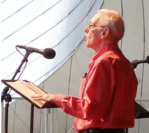 Photo of John Mahoney wearing a salmon colored shirt, talking into a microphone.
