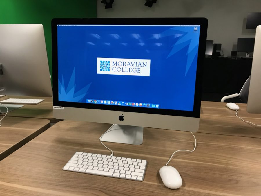 Photo of a Mac desktop computer screen with the Moravian College logo on the screen.