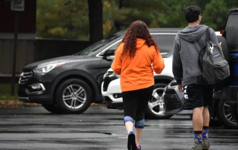 Commuter students Brianna Boggs and Cesar Corvera walk to their vehicles on a rainy day.