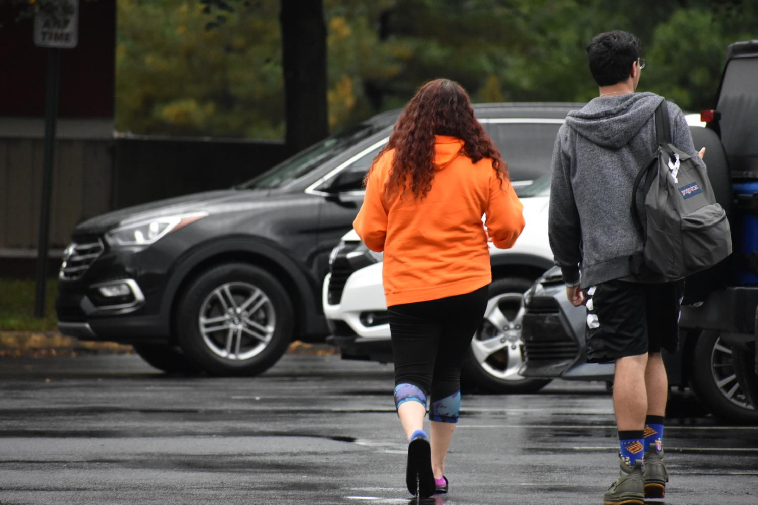 Commuter students Brianna Boggs and Cesar Corvera walk to their vehicles.