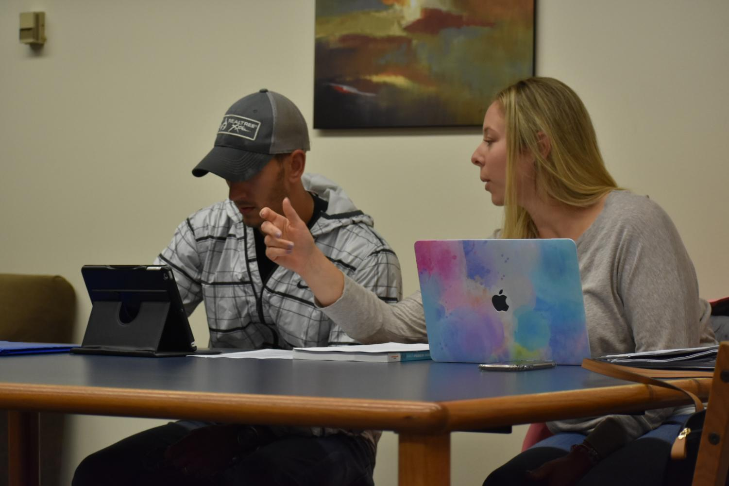 Kristina Szabo and John Pilla utilize their apple products to complete work in Reeves library.