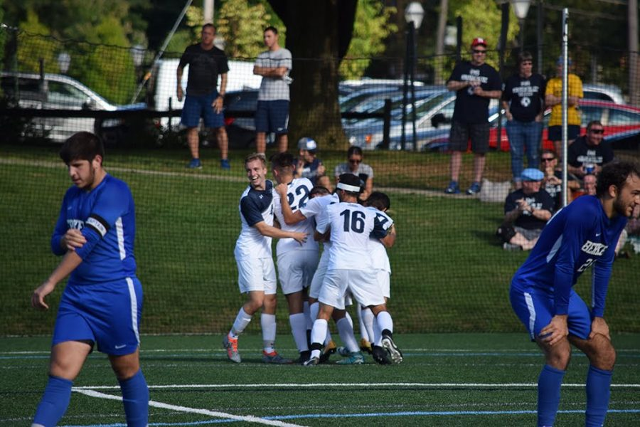 Members of the men's soccer team celebrate after a win.