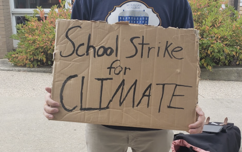 Brandon Faust, the leader of this strike on campus, holding a sign to protest climate change.