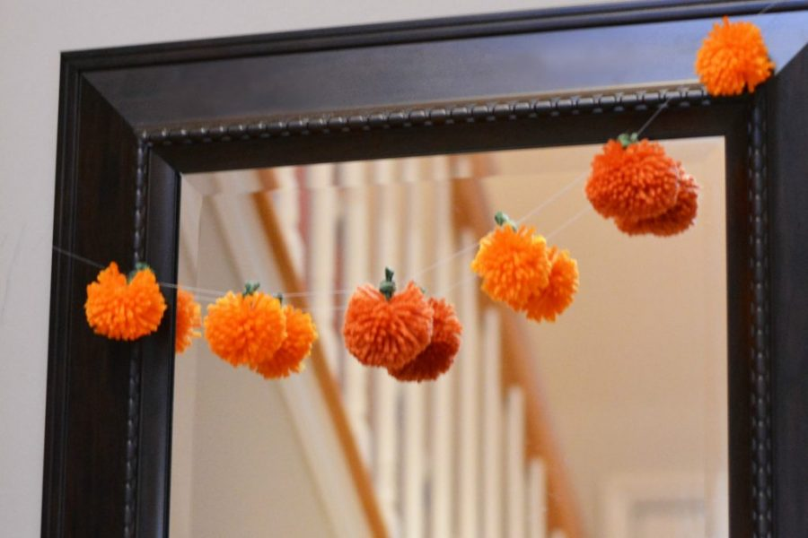 A string of pumpkins made from orange yarn.