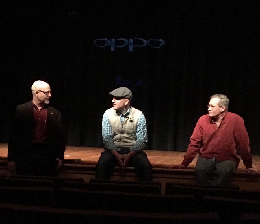 Photo features three men in dark lighting sitting and discussing with their hands moving.