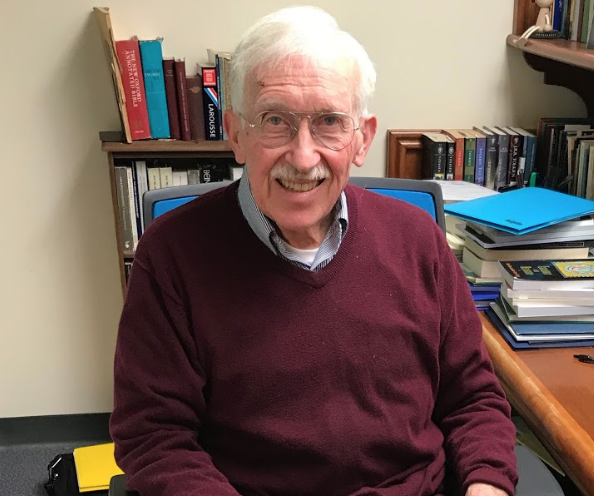Photo features Dr. Falla, a man with gray hair wearing a maroon sweatshirt with a background of brightly colored books.
