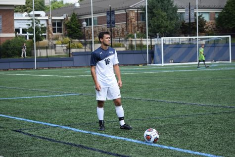 Mike Guarino is featured in a blue and white uniform on a lush green field waiting to kick a soccer ball.